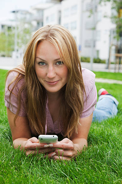 Portrait of smiling woman lying on grass and using mobile phone