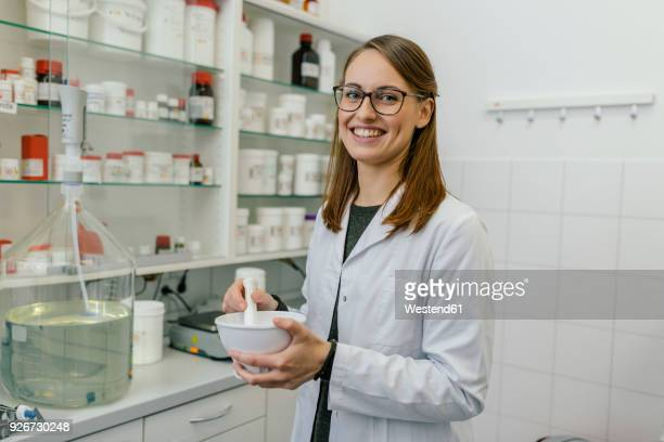 portrait of smiling woman making a salve in laboratory of a pharmacy - laborkittel stock-fotos und bilder
