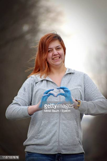 portrait of smiling woman making heart shape outdoors - baum stock pictures, royalty-free photos & images