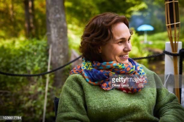 portrait of smiling woman on a houseboat looking sideways - einfaches leben stock-fotos und bilder