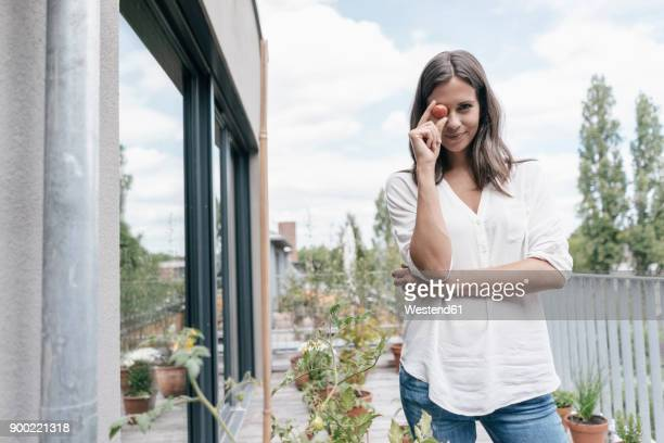 Portrait of smiling woman on balcony holding tomato