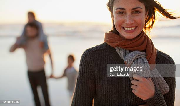 Portrait of smiling woman on beach with family in background