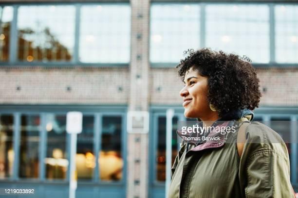 portrait of smiling woman on city street - カーキグリーン ストックフォトと画像