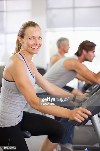Portrait of smiling woman on exercise machine in gymnasium