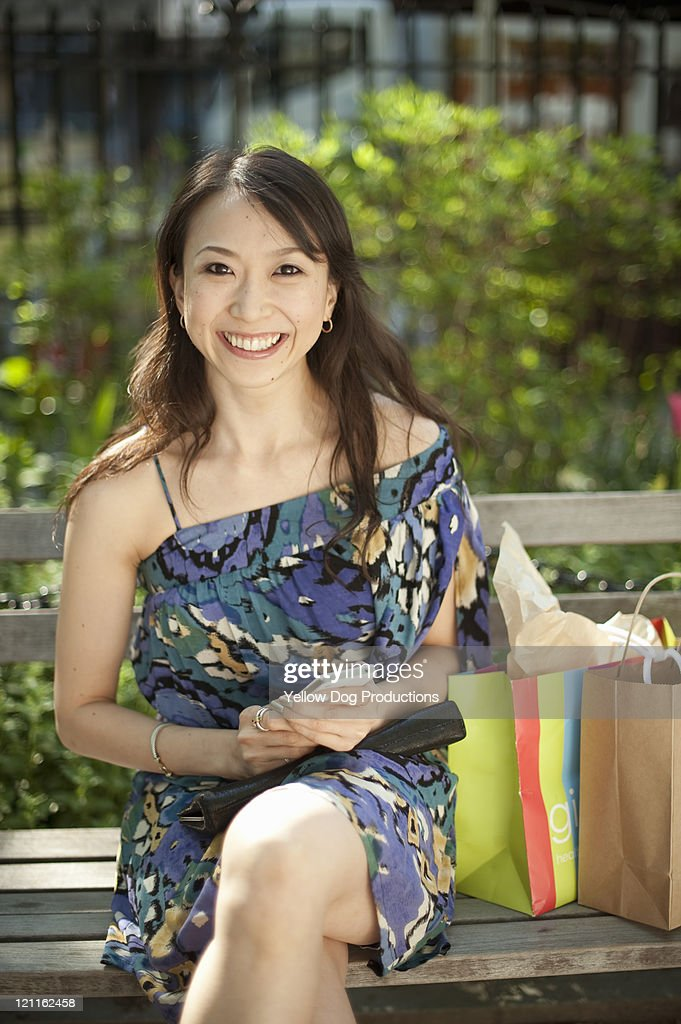 Portrait of smiling woman on park bench : Stockfoto
