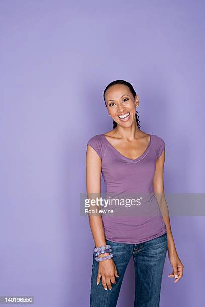 Portrait of smiling woman on purple background, studio shot