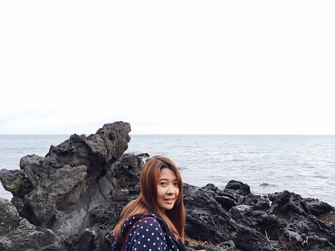 Portrait Of Smiling Woman On Rock By Sea Against Sky - gettyimageskorea