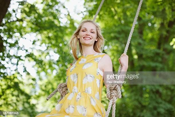 Portrait of smiling woman on swing under trees