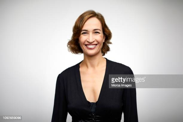 portrait of smiling woman on white background - 45 49 years stock pictures, royalty-free photos & images