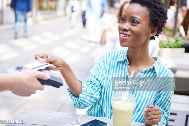 portrait of smiling woman paying by credit card at pavement cafe - contactless payment stock pictures, royalty-free photos & images