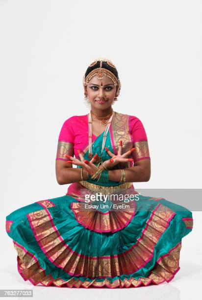 Portrait Of Smiling Woman Performing Bharatnatyam Against White Background