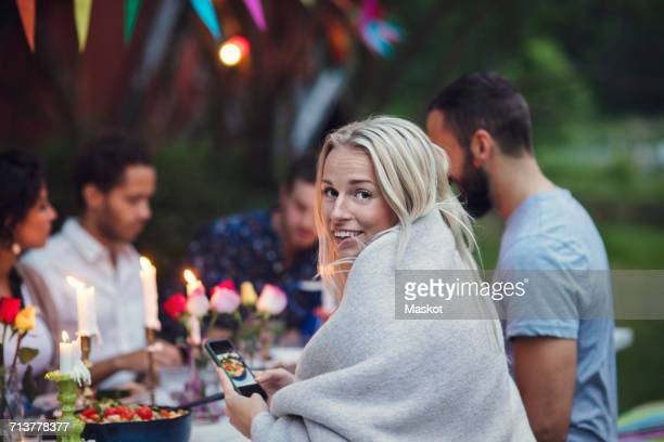 Portrait of smiling woman photographing food while sitting with friends at garden party