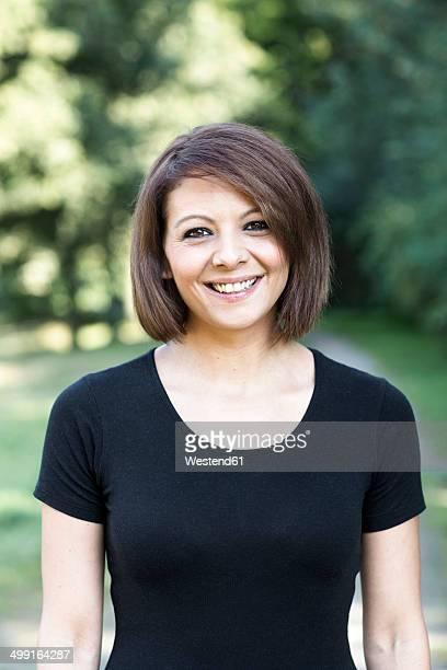 portrait of smiling woman - t shirt preta imagens e fotografias de stock