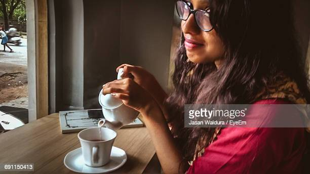 portrait of smiling woman pouring milk in tea at home - hot indian girls stock photos and pictures