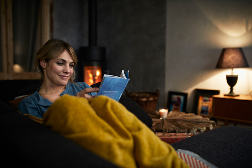 Portrait of smiling woman reading a book on couch at home in the evening - gettyimageskorea