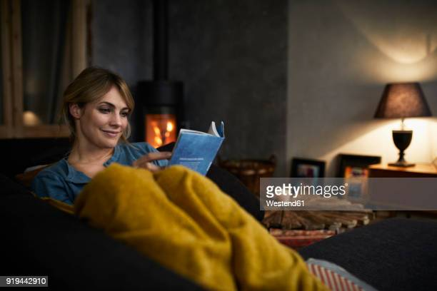 portrait of smiling woman reading a book on couch at home in the evening - avondschemering stockfoto's en -beelden