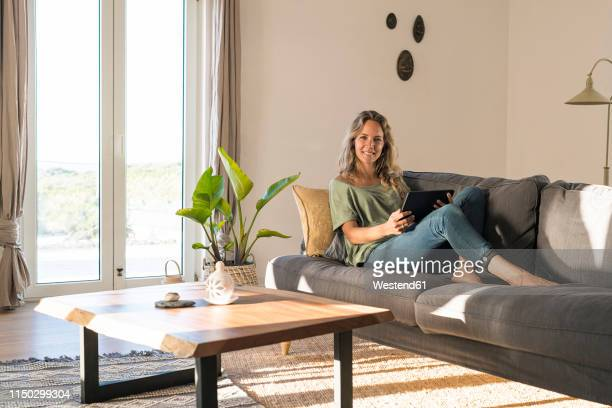 portrait of smiling woman realxing on couch at home with tablet - donne bionde scalze foto e immagini stock