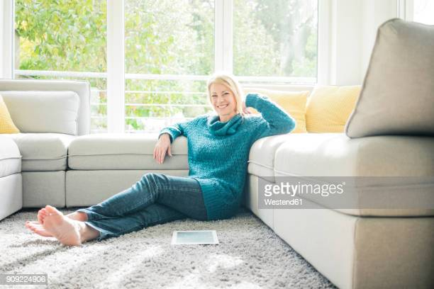 portrait of smiling woman relaxing in living room - donne bionde scalze foto e immagini stock