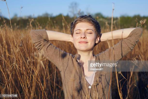portrait of smiling woman relaxing in nature - wolkenloser himmel stock-fotos und bilder