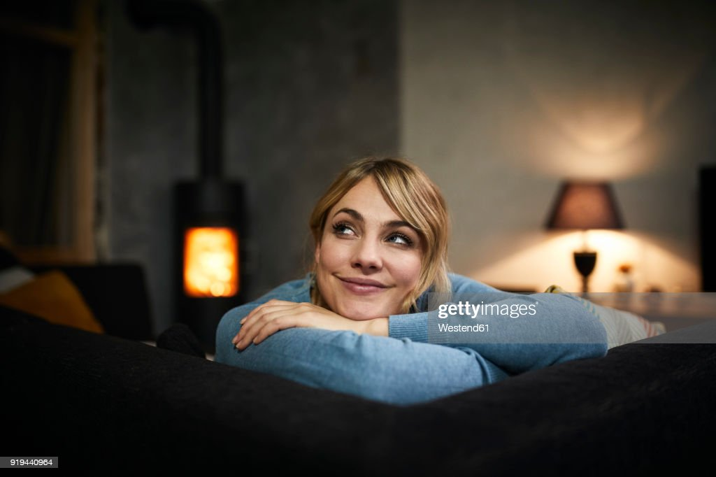 Portrait of smiling woman relaxing on couch at home in the evening : Stock-Foto