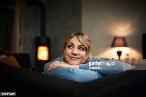 portrait of smiling woman relaxing on couch at home in the evening - calientes fotografías e imágenes de stock