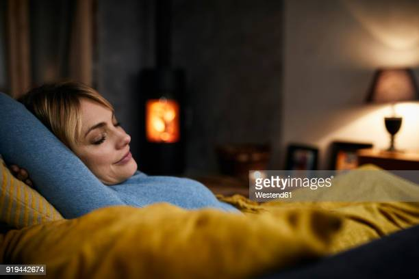 portrait of smiling woman relaxing on couch at home in the evening - undvikande bildbanksfoton och bilder