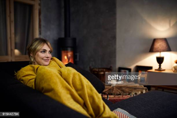 portrait of smiling woman relaxing on couch at home in the evening - gagged woman stock pictures, royalty-free photos & images