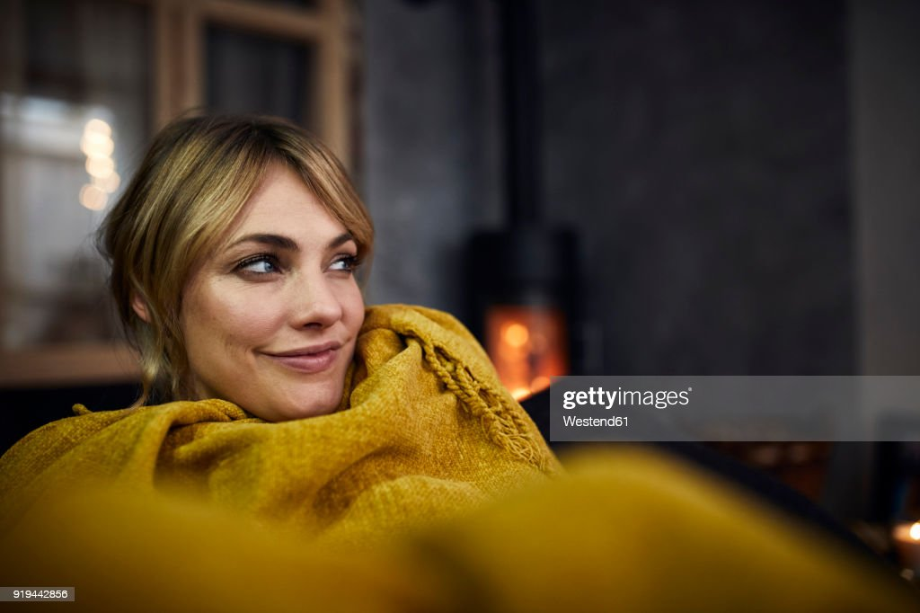 Portrait of smiling woman relaxing on couch at home in the evening : Stock Photo