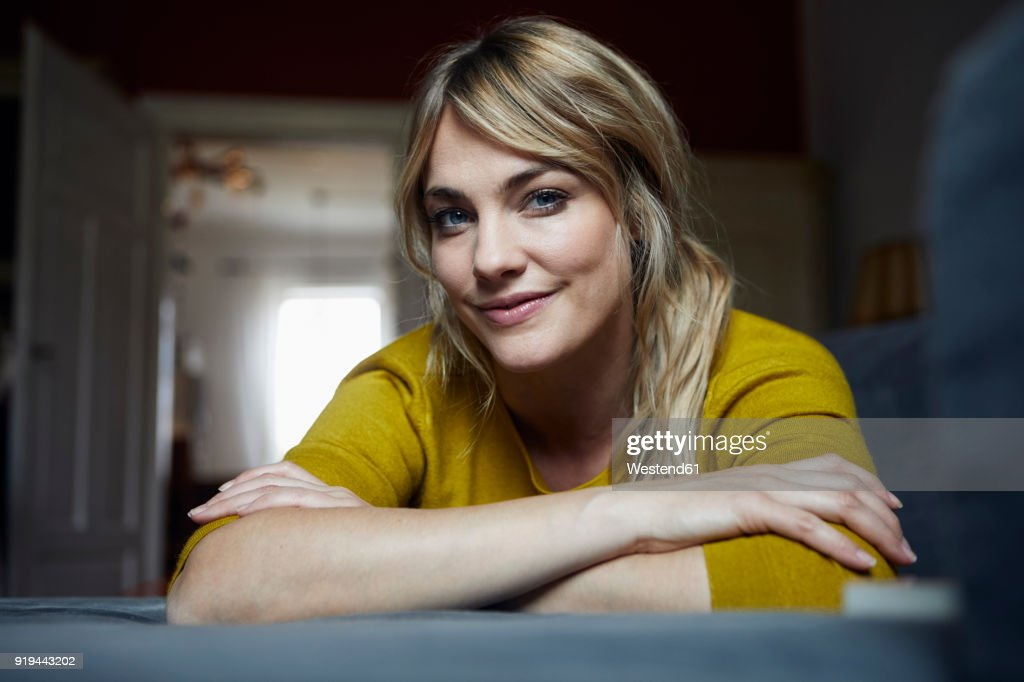Portrait of smiling woman relaxing on the couch at home : Stock Photo