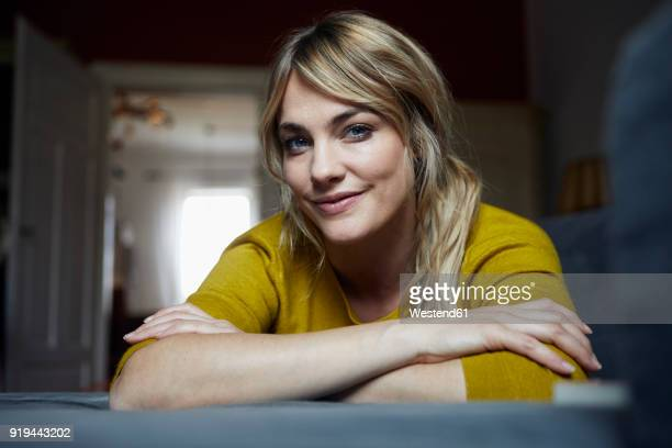 portrait of smiling woman relaxing on the couch at home - titta mot kameran bildbanksfoton och bilder