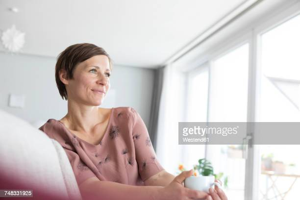 Portrait of smiling woman relaxing with cup of coffee at home