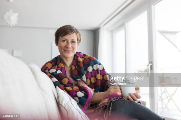 portrait of smiling woman relaxing with cup of coffee on the couch - mid adult women stock pictures, royalty-free photos & images
