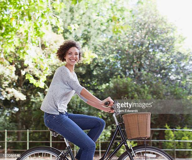 Retrato de mujer sonriente montar bicicleta en el parque