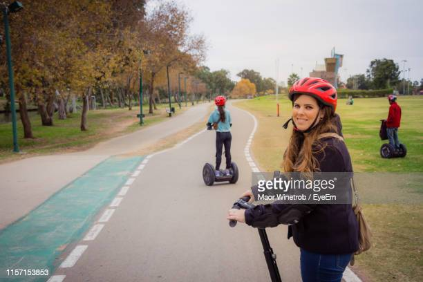 portrait of smiling woman riding hoverboard on road - hoverboard stock pictures, royalty-free photos & images