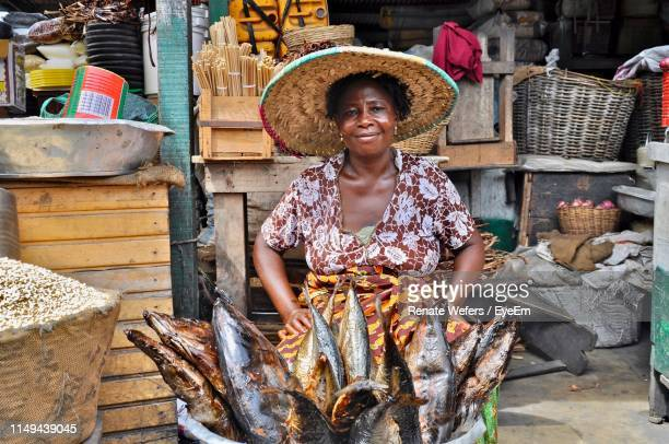 portrait of smiling woman selling fish at market - ghana stock pictures, royalty-free photos & images
