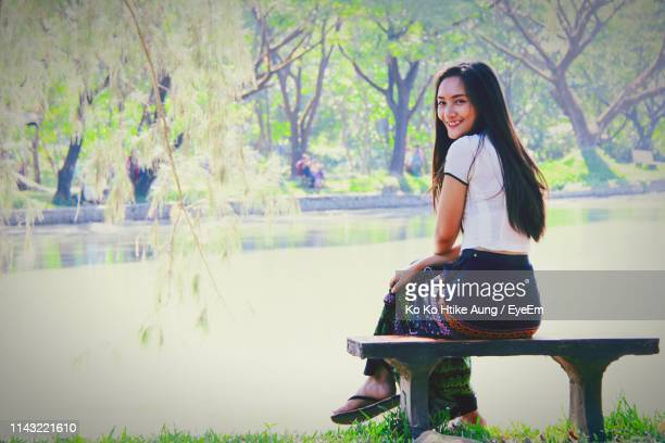 portrait of smiling woman sitting against lake - ko ko htike aung stock pictures, royalty-free photos & images