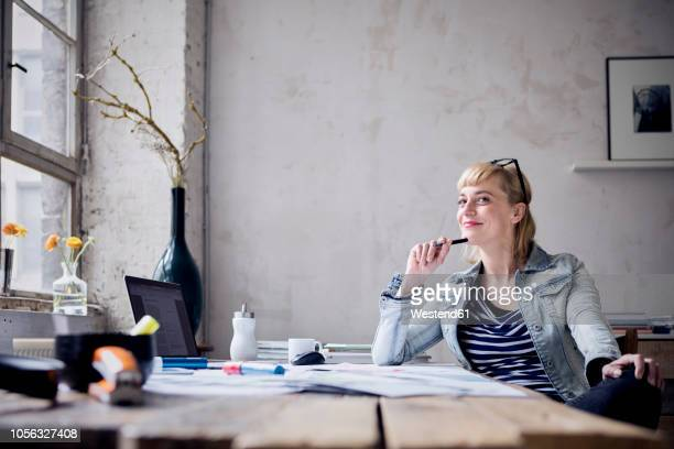 portrait of smiling woman sitting at desk in a loft - laptop mockup stock photos and pictures