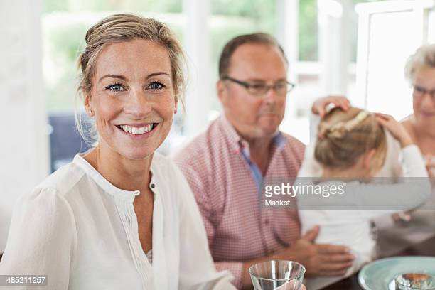Portrait of smiling woman sitting at dining table with family