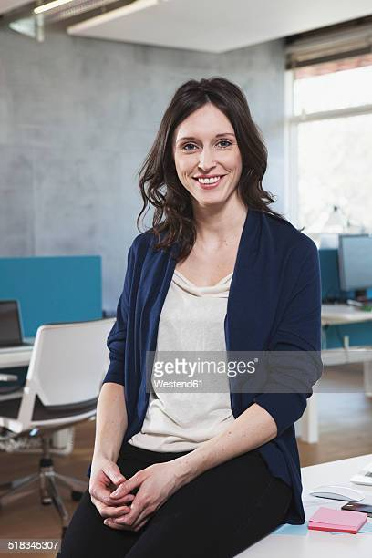 Portrait of smiling woman sitting at her workplace in the open space office