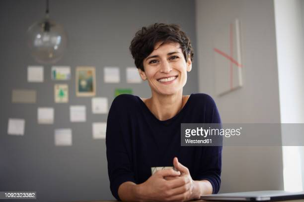 portrait of smiling woman sitting at table at home - kurzes haar stock-fotos und bilder