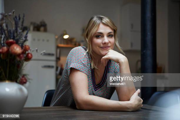 Portrait of smiling woman sitting at table in the kitchen