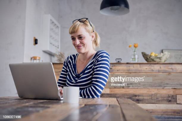 Portrait of smiling woman sitting at table using laptop