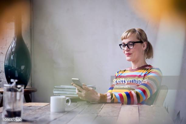 portrait of smiling woman sitting at table with cup of coffee looking at cell phone - blonde glasses stock-fotos und bilder