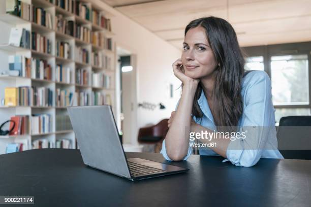 portrait of smiling woman sitting at table with laptop - in den dreißigern stock-fotos und bilder