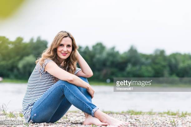 portrait of smiling woman sitting at the riverside - ボーダーシャツ ストックフォトと画像