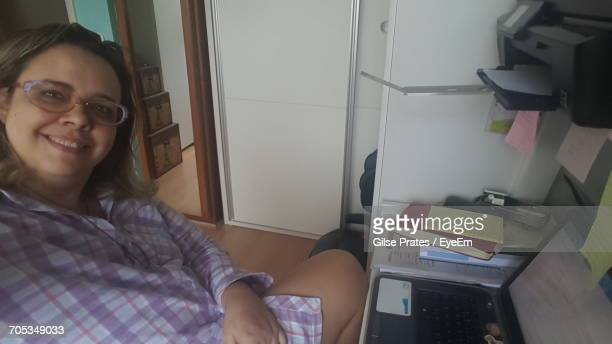 portrait of smiling woman sitting by laptop on table at home - a prates a foto e immagini stock