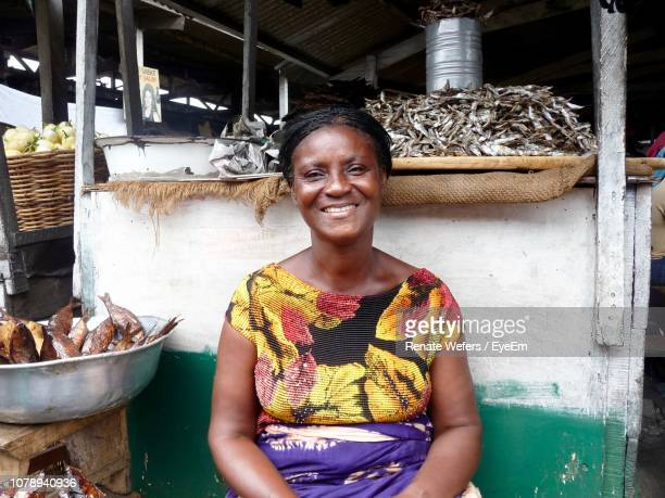 portrait of smiling woman sitting by seafood at market - ghana africa fotografías e imágenes de stock