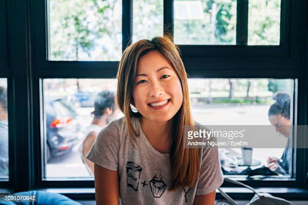 portrait of smiling woman sitting in cafe - 30 34 years stock pictures, royalty-free photos & images