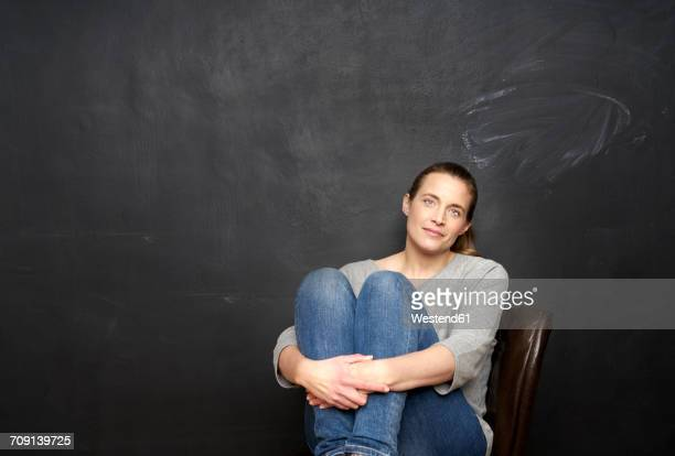 Portrait of smiling woman sitting in front of blackboard