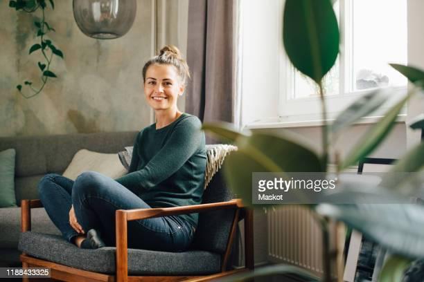 portrait of smiling woman sitting on armchair at home - wohnung stock-fotos und bilder